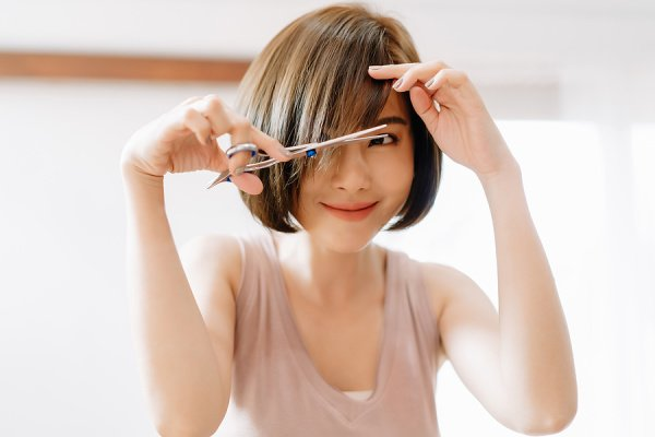 How to Cut Your Own Bangs | If you're looking for step-by-step instructions to help you learn how to cut bangs at home, this post has XX tips and tutorials to help! Whether you want to trim your own bangs in between haircuts, or you're cutting bangs for the first time, this post has everything you need to know. From layered bangs, to blunt bangs, to side swept bangs, to face-framing bangs, to layered bangs, we've curated the best hair cutting tools, products, and techniques to help!